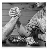 Men arm wrestling over money