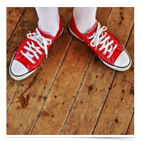 Red Converse on a wooden floor.