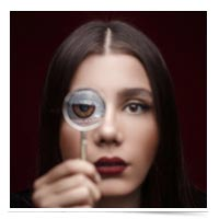 Woman peering through magnifying glass.