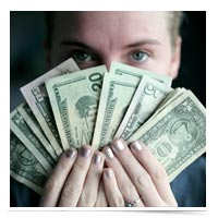 Woman holding up US cash.