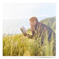 Man reading by a lake.