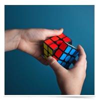 Hands solving a Rubix cube.