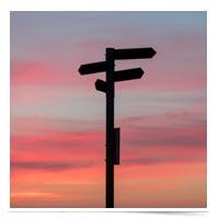 Directional road signs at sundown.